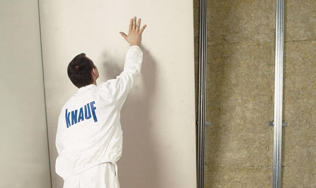 Mężczyzna montuje płytę gk, by stworzyć ścianę działową.